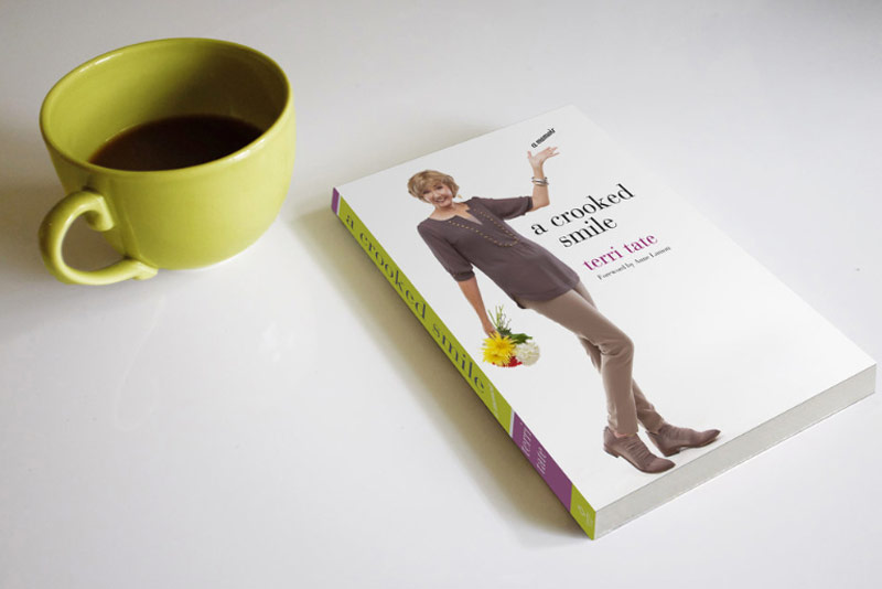 an image of a coffee cup on a table next to a book titled A Crooked Smile