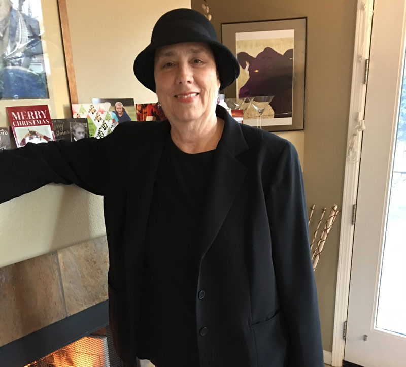 image of Casey Hobbs in a dark blazer, skinny jeans, and cute hat standing in front of her fireplace
