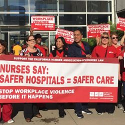 an image of a large group of nurses picketing and protesting with large red signs and bright red shirts