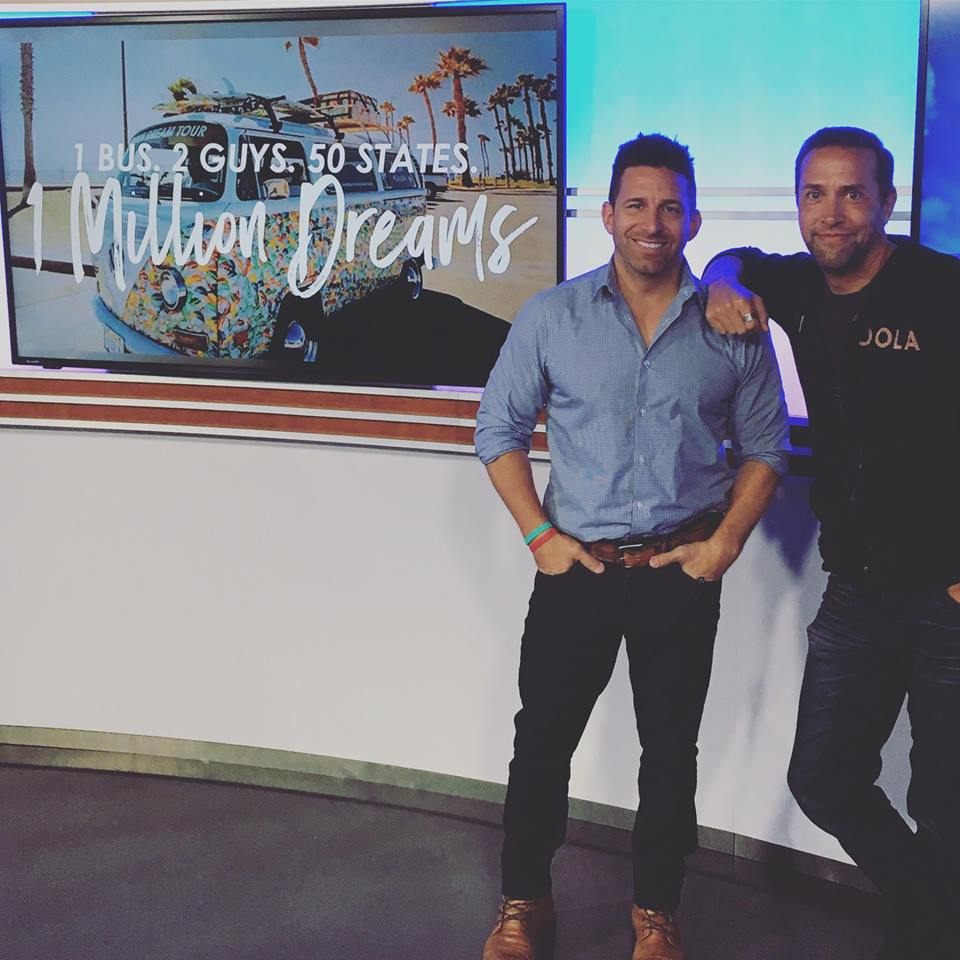 an image of Dave Braun and Troy Amdahl standing in front of their 1 bus 2 guys 50 states poster.