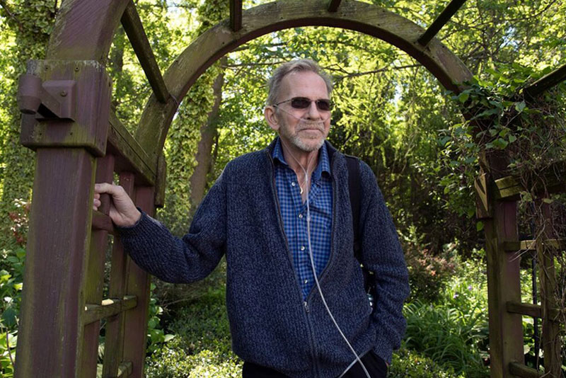 an image of an older man who has cancer standing outdoors wearing a blue sweater and dark sunglasses with his oxygen tank and line around his ears and nose