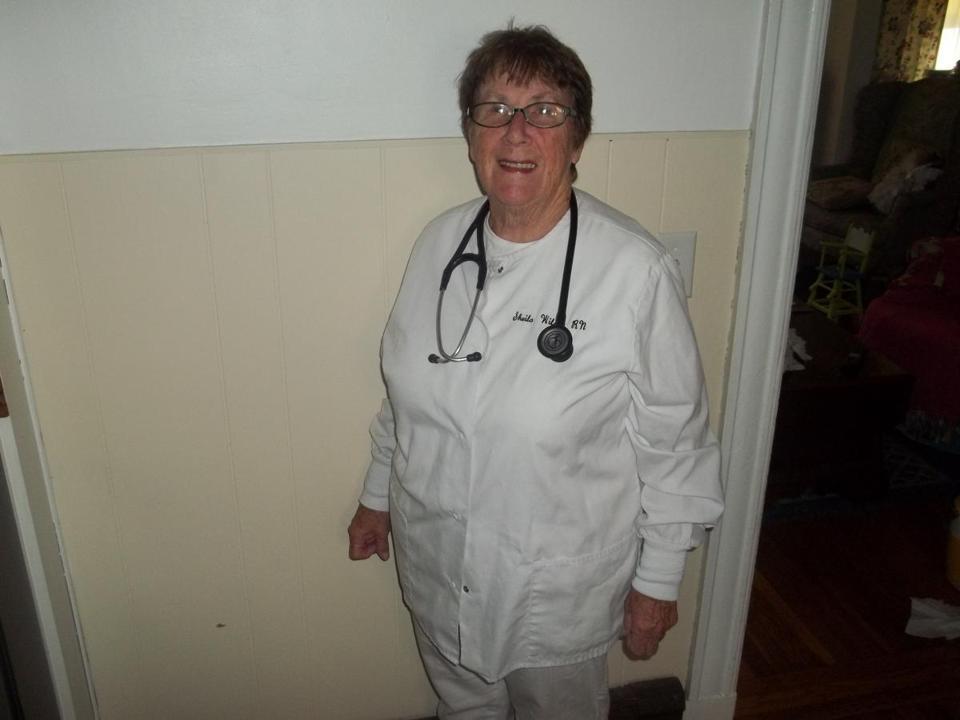 an image of an elderly female nurse with a short haircut in white nurses' scrubs