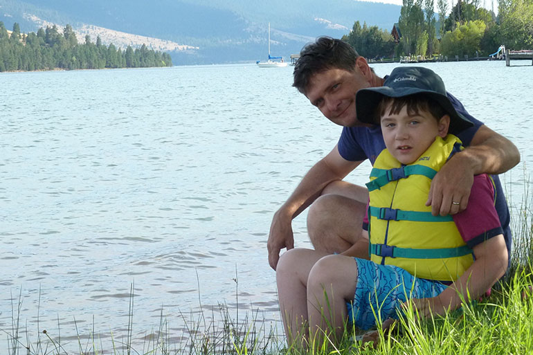 an image of a middle aged man sitting next to a young boy in a bright yellow life jacket on the shore of a very large lake