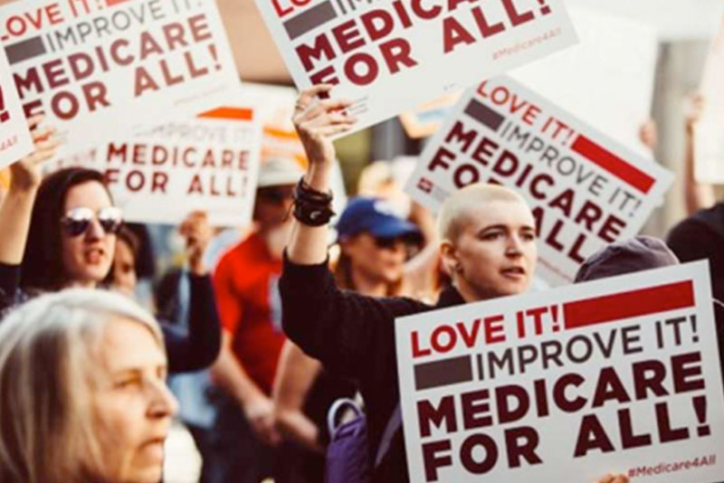 protesters holding medicare for all signs