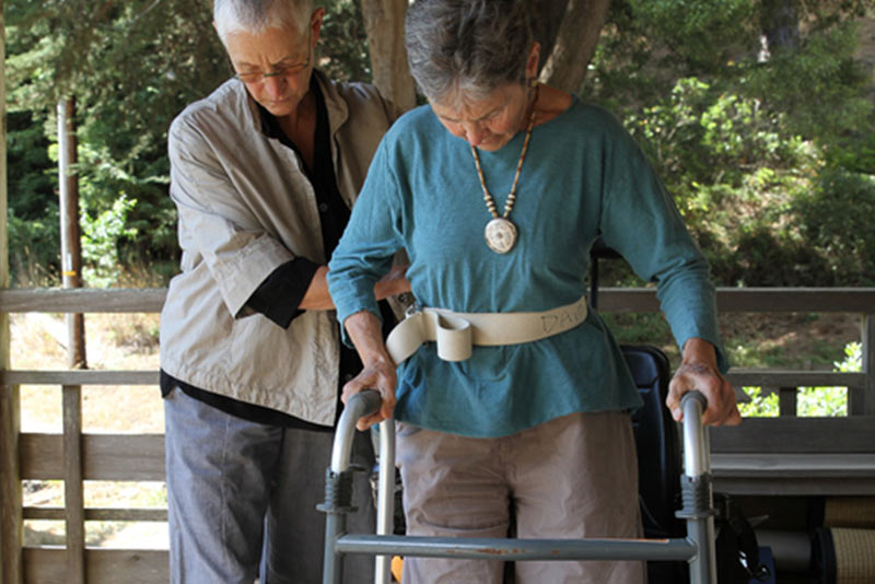 an outdoor image of two women, one is helping the other with her walker as she attempts to take some steps