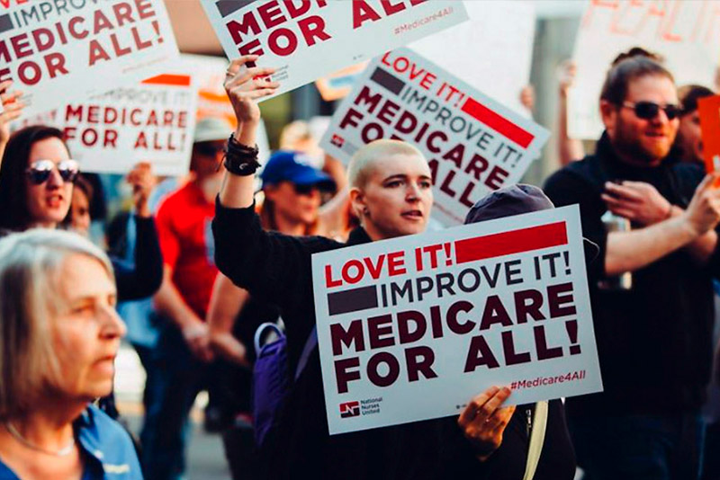 an image of a large group of people protesting and demonstrating outdoors for single payer healthcare